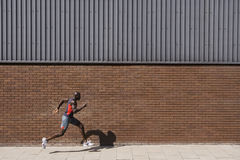 Man Running Past Brick Wall Stock Image
