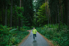 Man running on path in an old green forest. Stock Photography