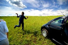 Man Running Playfully In Field. Man is running playfully through the field, near his parked car. The door on the passenger side is open. His female companion is royalty free stock photo
