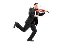 Man running and playing a violin Stock Photo