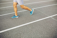 Man running on a racing track Stock Images