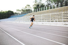Man running on a racing track Stock Photos