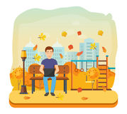 Man running remotely on freelance, on bench in autumn park. Royalty Free Stock Photography