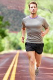 Man running on road - Sport and fitness runner. Man running on road. Sport and fitness runner training for marathon run doing workout outdoors in summer. Male Royalty Free Stock Images