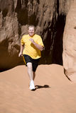 Man running in sand with yellow shirt. A man running in the sand Royalty Free Stock Photo