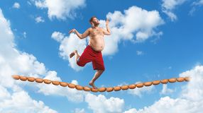 Man running on the sausage rope Stock Photos