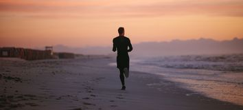 Man running by the sea in morning. Rear view shot of fit man running on the sea shore in morning. Healthy male athlete running along the beach royalty free stock photos