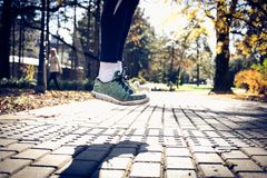Man running shoes in the move. Sporty man jumping in park Royalty Free Stock Photo