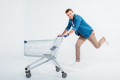 Man running with shopping trolley and smiling at camera. Happy young man running with shopping trolley and smiling at camera Stock Image