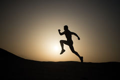 Man running silhouette at sunset, young caucasian run in mountain Royalty Free Stock Photos