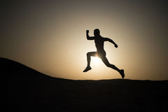 Man running silhouette at sunset, young caucasian run in mountain. Man running silhouette on sunset background, young caucasian run in mountain Royalty Free Stock Photo