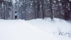 Man running on snow covered winter road in forest stock video footage