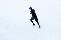 Man running on the snow Stock Photos
