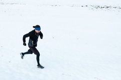 Man running on the snow Royalty Free Stock Photos