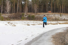 The man running on snow on the river bank Stock Photography