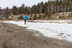 The man  running on snow on the river bank Stock Images