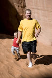 Man running with son. A father holding his sons hand while running in the sand Stock Photo