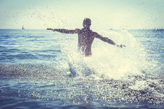 Man running splashing ocean sea water. Fun Royalty Free Stock Photography
