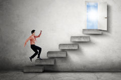 Man running on stairs leads a door Royalty Free Stock Photos