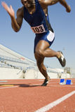 Man Running From Starting Block. Low section of men running from starting block on track Stock Photo