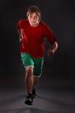 Man running on studio black background. Stock Images