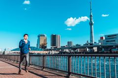 Man running by Sumida river, Tokyo Skytree in background. Sport training, healthy lifestyle, or Tokyo 2020 summer Olympic concept stock photography