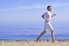 Man running on sunny beach. Unrecognizable body jogging on ocean beach. Running on tropical beach. Attractive man enjoying nature. Stock Photos