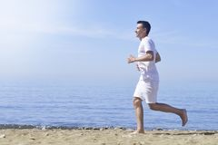 Man running on sunny beach. Unrecognizable body jogging on ocean beach. Running on tropical beach. Attractive man enjoying nature. Stock Image