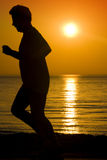 Man Running at Sunrise. A silhouette of a man running on the beach at sunrise Royalty Free Stock Photography