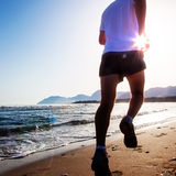 Man running at sunset on a sandy beach in a sunny day Royalty Free Stock Photography