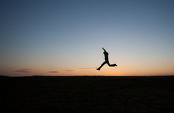 Man running in sunset sky on hill Stock Images