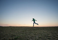 Man running in sunset sky on hill Stock Photos