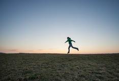 Man running in sunset sky on hill stock photos