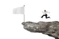 Man running to blank flag on cliff with white Stock Image