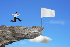 Man running to blank white flag on cliff with sky Royalty Free Stock Photography