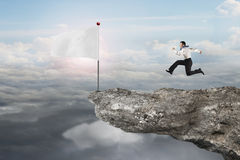 Man running to blank white flag on cliff with sunlight Stock Photography