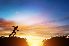 Man running to jump over precipice between two mountains Royalty Free Stock Photography