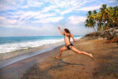Man running to the ocean. Happy screaming man with long hair running on the beach to the ocean at palms background Royalty Free Stock Photography