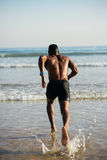 Man running to the sea for swimming training Stock Photos