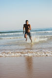 Man running to the sea for swimming training Royalty Free Stock Photography