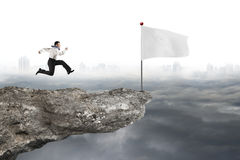 Man running to white flag on cliff with cloudy cityscape Royalty Free Stock Photography