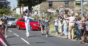 Man running with torch. Olympic torch relay Royalty Free Stock Image