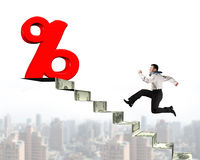 Man running toward percentage sign on top of money stairs Royalty Free Stock Images