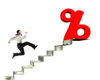 Man running toward percentage sign on top of money stairs Royalty Free Stock Photography