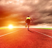 Man running on the track with sunrise background Stock Photo