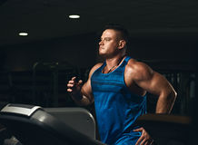 Man on running track. Young handsome athletic man in sportswear running on treadmill at gym Stock Photography