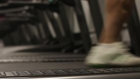 Man running on a treadmill. Close up shot. Focus on leg. Man running in a modern gym on a treadmill concept for exercising, fitness and healthy lifestyle stock footage