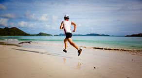 Man running on a tropical beach Royalty Free Stock Photos