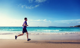 Man running on tropical beach Royalty Free Stock Images