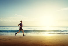 Man running on tropical beach at sunset Royalty Free Stock Photography